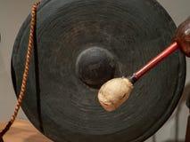 El mazo se prepara para pegar un gongo asiático antiguo imagen de archivo