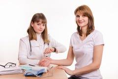 El médico en la tabla comprueba el pulso de un paciente Fotografía de archivo libre de regalías