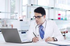 El médico escribe la prescripción en laboratorio Imagen de archivo