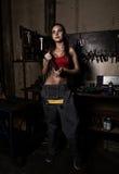 El mecánico atractivo de la muchacha se coloca al lado de un banco de trabajo, deteniendo a una llave inglesa en su mano en repar Foto de archivo libre de regalías