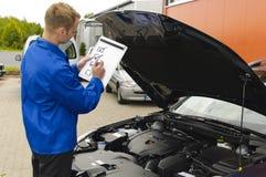 El mecánico auto controla un vehículo Foto de archivo