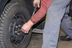 El mecánico cambia los neumáticos Fotos de archivo