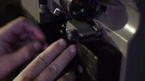 El mecánico carga la película en un proyector de película viejo Primer de un carrete con una película metrajes