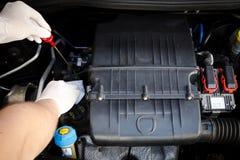 El mecánico comprueba el nivel de aceite Fotografía de archivo libre de regalías
