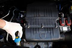El mecánico comprueba el nivel líquido del líquido refrigerador Imagen de archivo libre de regalías