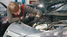 El mecánico comprueba el motor de automóvil, reparación del coche, trabajando en el taller, revisión, debajo de la capilla metrajes