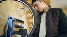 El mecánico concentrado está mirando la rueda de bicicleta giratoria que comprueba los rayos entonces que los enderezan con las h almacen de metraje de vídeo