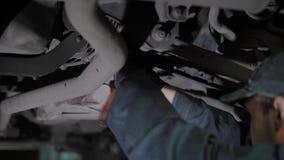 El mecánico de automóvil está regulando el cable del freno de mano, colocándose debajo del coche levantado, aprieta los detalles  almacen de video