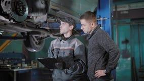 El mecánico de automóvil está valorando un disco de freno, las zapatas de freno y la manguera, explicando para un propietario de  almacen de metraje de vídeo
