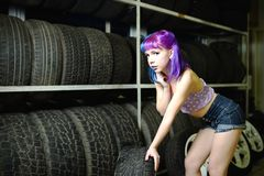 El mecánico de automóvil hermoso de la muchacha del inconformista trabaja con los neumáticos en las ruedas foto de archivo