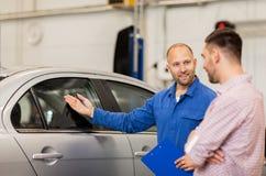 El mecánico de automóviles con el tablero y el hombre en el coche hacen compras Imagenes de archivo