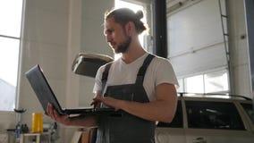 El mecánico de automóviles del retrato en el contraluz, gasolinera, los trabajos masculinos del amo sobre el ordenador portátil c almacen de metraje de vídeo