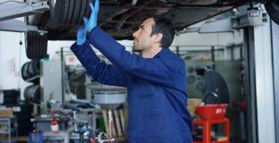 El mecánico de automóviles en el servicio del coche, reparaciones del especialista el coche, hace la transmisión y las ruedas Con fotografía de archivo