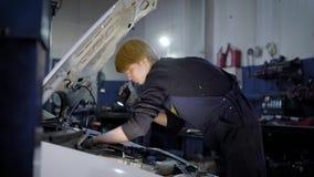 El mecánico de automóviles está comprobando faltas internas en sistemas del coche y la robustez importantes de conexiones, en la  metrajes