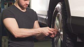 El mecánico de automóviles está torciendo manualmente emperna de las ruedas en un automóvil, aumentado por el equipo de elevación metrajes