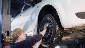 El mecánico de automóviles está torciendo manualmente emperna de las ruedas en un automóvil, aumentado por el equipo de elevación almacen de video
