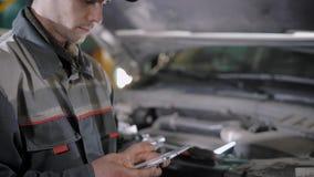 El mecánico de automóviles está utilizando la tableta para el valor calculador para una reparación del coche y está llenando enci almacen de metraje de vídeo