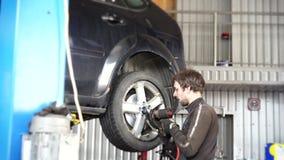 El mecánico de automóviles fortalece la rueda con una llave de impacto almacen de metraje de vídeo