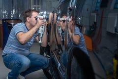 El mecánico de automóviles pule el coche en servicio auto imágenes de archivo libres de regalías