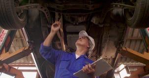 El mecánico de automóviles de sexo masculino examina la manera del tren de aterrizaje del coche en garaje almacen de metraje de vídeo