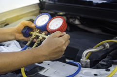 El mecánico de automóviles utiliza un indicador de presión en el compresor de aire, líquido foto de archivo