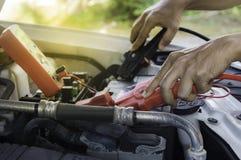 El mecánico de automóviles utiliza una batería de carga con ju del canal de la electricidad fotos de archivo
