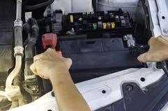 El mecánico de automóviles utiliza una batería de carga con ju del canal de la electricidad imagen de archivo libre de regalías