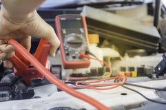 El mecánico de automóviles utiliza una batería de carga con ju del canal de la electricidad foto de archivo libre de regalías