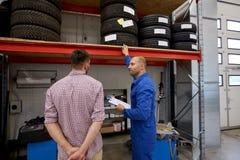El mecánico de automóviles y el hombre con los neumáticos en el coche hacen compras Fotografía de archivo libre de regalías