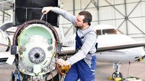 El mecánico de aviones repara un motor de avión en un hanga del aeropuerto fotos de archivo libres de regalías