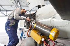 El mecánico de aviones repara un motor de avión en un hanga del aeropuerto imágenes de archivo libres de regalías