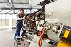 El mecánico de aviones repara un motor de avión en un hanga del aeropuerto foto de archivo