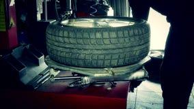 El mecánico de coche desmonta el neumático del borde de la rueda con el equipo especial almacen de video
