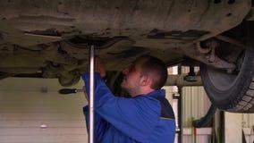 El mecánico de coche en traje examina el cuerpo del coche en la elevación del coche en primer del garge metrajes