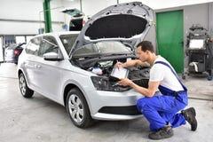 El mecánico de coche examina el vehículo en un taller fotos de archivo libres de regalías
