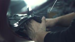 El mecánico de coche instala la malla protectora almacen de metraje de vídeo