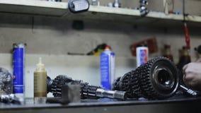 El mecánico de coche lubrica el mecanismo de la transmisión en el garaje metrajes
