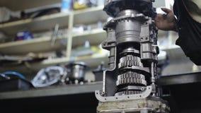 El mecánico de coche lubrica el mecanismo de la transmisión en el garaje almacen de video