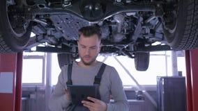 El mecánico de coche profesional examina el automóvil en la elevación durante la reparación y escribe notas en la gasolinera almacen de video
