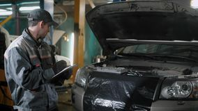 El mecánico de coche se está colocando en un taller de reparaciones auto cerca del automóvil con la capilla abierta y está hacien almacen de video