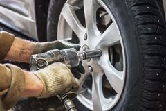 El mecánico de coche substituye las ruedas de coche del automóvil levantado por la llave neumática en la estación del garaje de l fotos de archivo