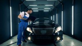 El mecánico de sexo masculino se está colocando cerca de un automóvil negro con un ordenador portátil almacen de metraje de vídeo