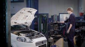 El mecánico del motor está diagnosticando el automóvil durante la inspección y está incorporando datos en el ordenador en un tall almacen de metraje de vídeo