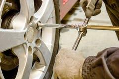 El mecánico desatornilla la llave de la rueda Fotos de archivo