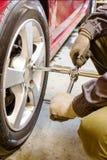El mecánico desatornilla la llave de la rueda Imagen de archivo