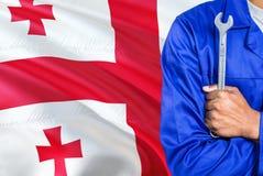 El mecánico georgiano en uniforme azul está sosteniendo la llave contra agitar el fondo de la bandera de Georgia Técnico cruzado  imagen de archivo