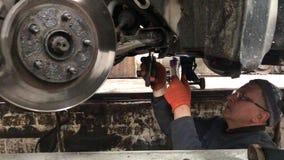 El mecánico hace la diagnosis del coche en el taller almacen de metraje de vídeo