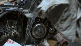 El mecánico hace preparaciones antes de fijar el motor dañado metrajes