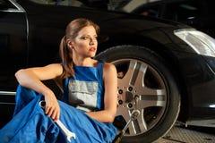 El mecánico hermoso de la muchacha se sienta cerca de la rueda del coche negro Fotografía de archivo