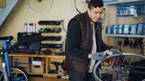 El mecánico hermoso está limpiando la rueda de bicicleta afuera y dentro, el eje y los rayos con el pedazo de paño y está escucha almacen de video